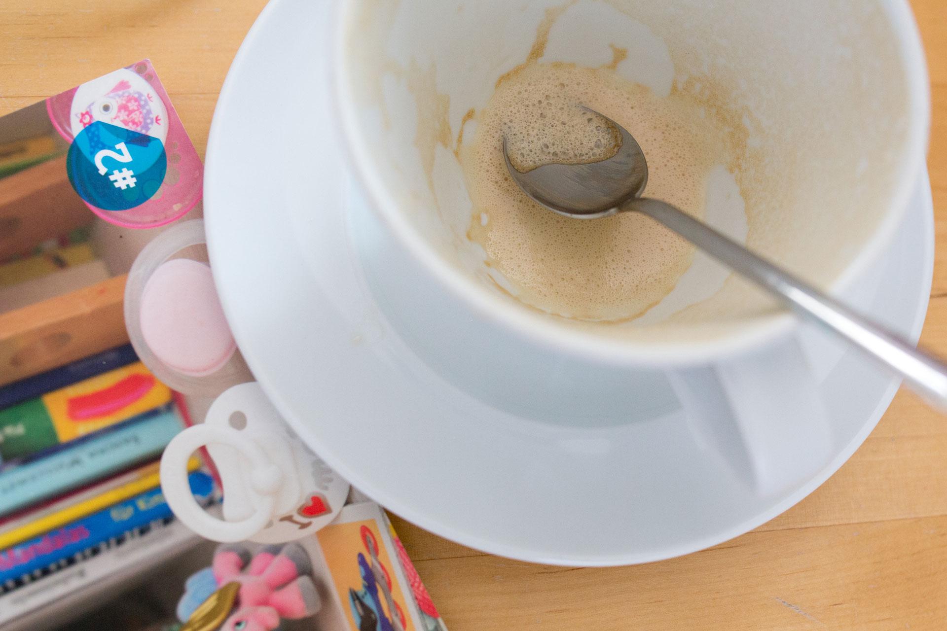 Leere Kaffeetasse, daneben liegen Schnuller und eine Broschüre
