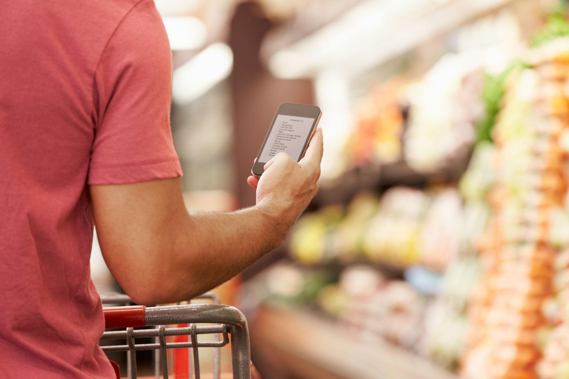 Mann hakt beim Einkaufen den digitalen Einkaufszettel ab